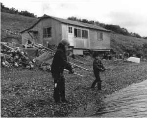 two-boys-fishing-in-front-of-old-cabin
